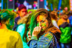 a girl with greed, yellow, red and blue paint on her face