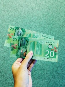 Person holding Canadian banknotes.