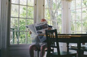 man reading newspaper while sitting on chair