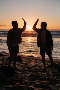 silhouette of two men near seashore about to high five during sunset