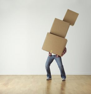 a man carrying three moving boxes in his arms which are covering his torso
