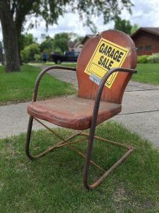 an old red chair with a garage sale sign on it