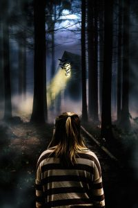 a girl standing in front of a haunted house in the woods